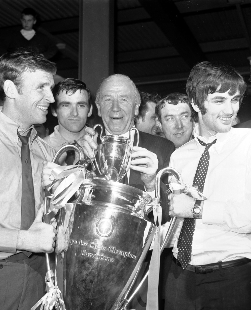 FILE - In this May 30, 1968 file photo, Pat Crerand, left, and George Best, right, of Manchester United hold the European Cup with their manager Matt ...