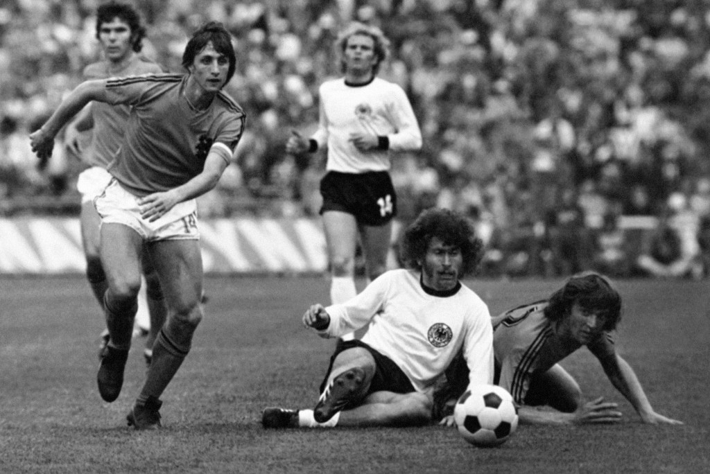 FILE - In this July 7, 1974 file photo, Dutch forward Johan Cruyff, left, runs past German defender Paul Breitner, sitting on the pitch during the Wor