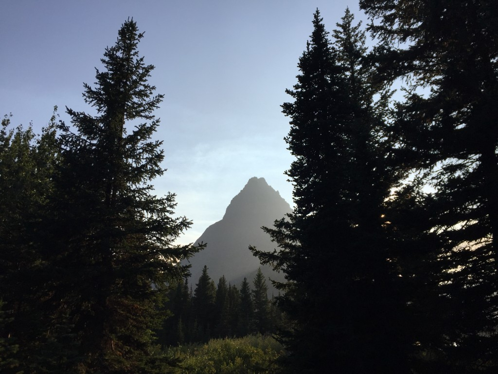 A mountain peak is seen behind tall trees in this Sept. 4, 2017 photo from Glacier National Park in Montana. The National Park Service says that the p...