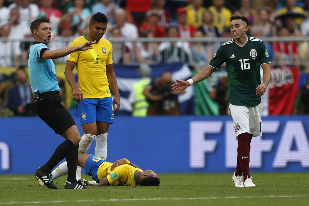 Brazil's Neymar lies on the ground besides referee Gianluca Rocchi during the round of 16 match between Brazil and Mexico at the 2018 soccer World Cup