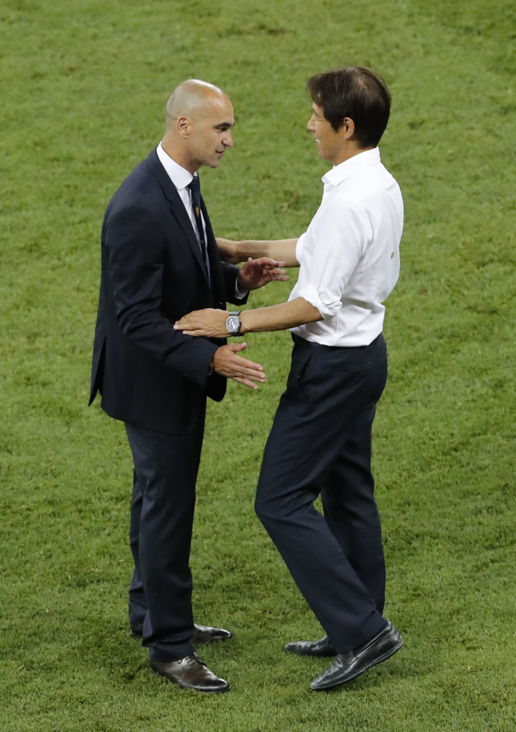 Belgium coach Roberto Martinez, left, greets Japan's head coach Akira Nishino at the end of the round of 16 match between Belgium and Japan at the 201
