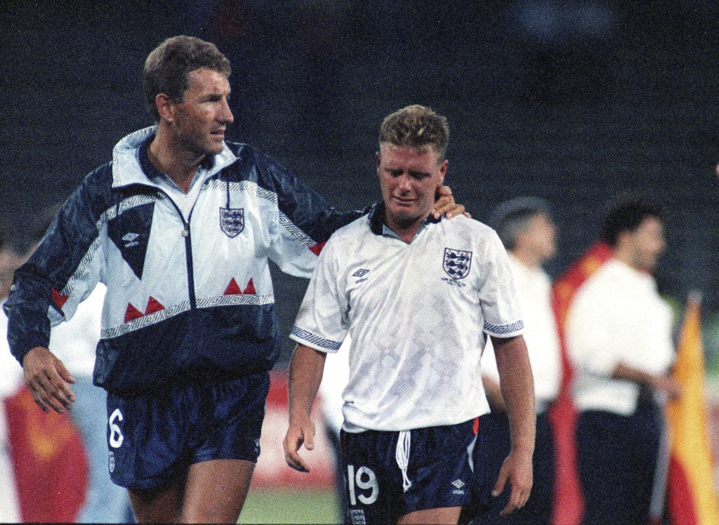 FILE - The July 4, 1990 file photo shows England's Paul Gascoigne crying as he is escorted off the field by team captain Terry Butcher, after his Engl...