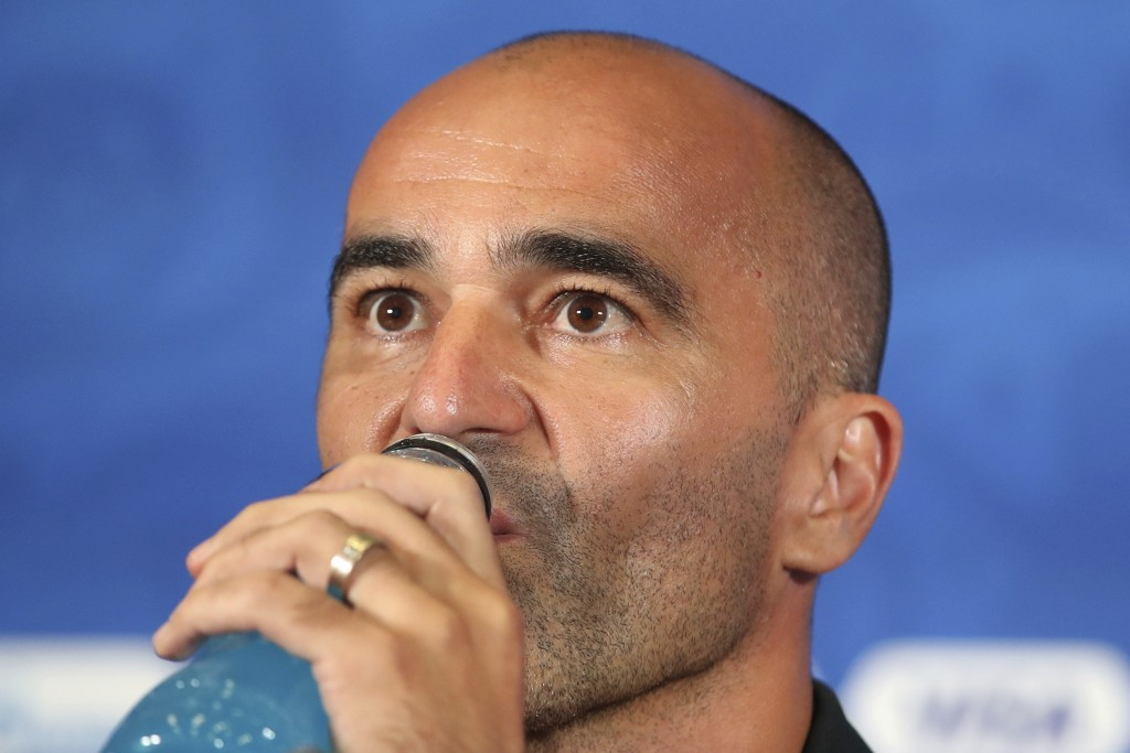 Belgium coach Roberto Martinez drinks an energy drink during the official press conference at the eve of their quarterfinal match against Brazil at th...