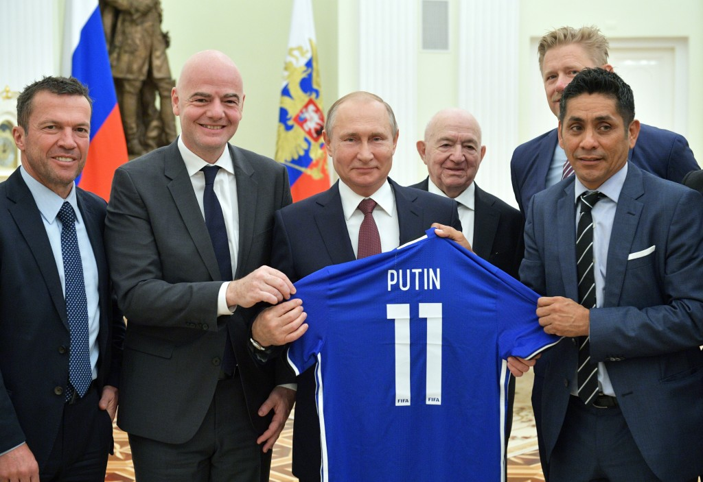 Russian President Vladimir Putin, center, poses for a photo with world soccer legends, former German soccer player Lothar Matthaus, left, FIFA Preside