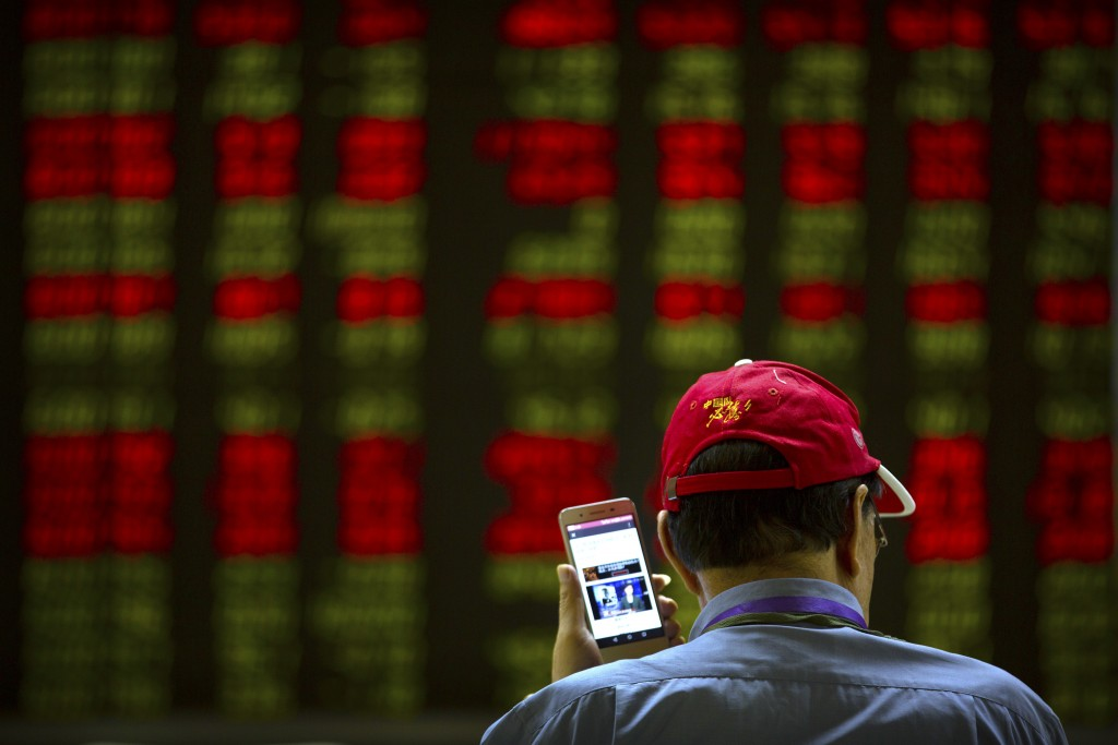 A Chinese investor listens to a news report on his smartphone as he monitors stock prices at a brokerage house in Beijing, Friday, July 6, 2018. Presi...