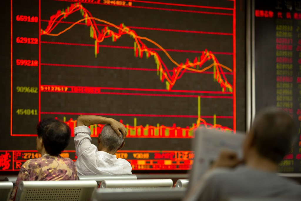 Chinese investors monitor stock prices at a brokerage house in Beijing, Friday, July 6, 2018. President Donald Trump made clear Thursday that U.S. tar...