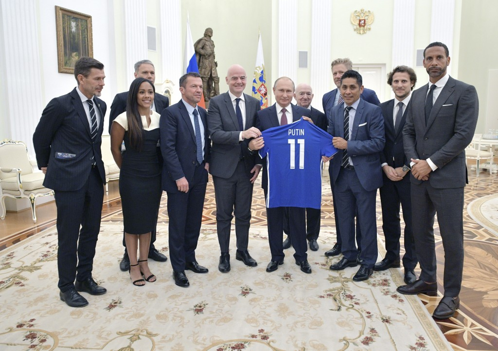 Russian President Vladimir Putin, center right, and FIFA President Gianni Infantino, center left, pose for a photo with world soccer legends during a