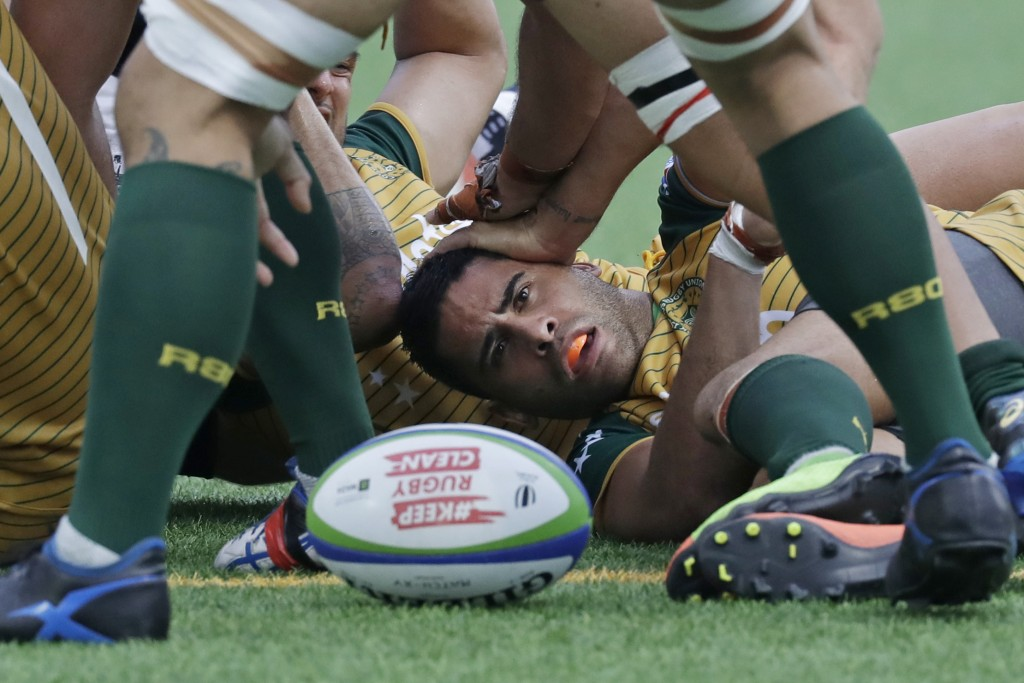 In this Saturday, July 7, 2018, file photo, Brynn Uriarau of Cook Islands is tackled by Hong Kong's rugby team during their play off match of the qual