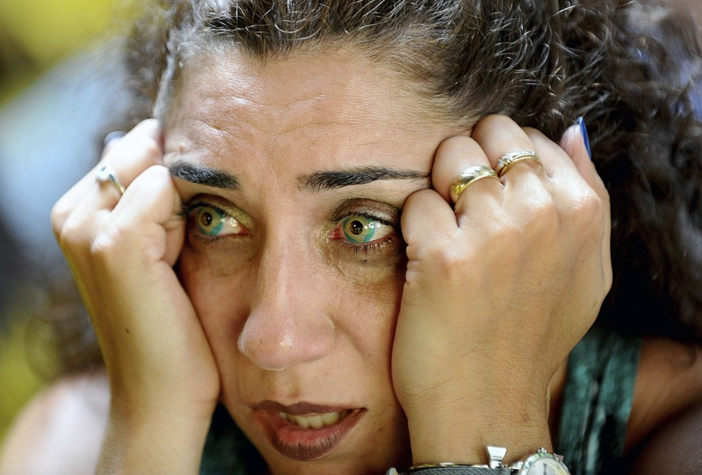 Wearing Brazilian flag contact lenses, Brazilian soccer fan Elizangela Santos, of Clinton, Mass., reacts after watching television coverage of Brazil'...
