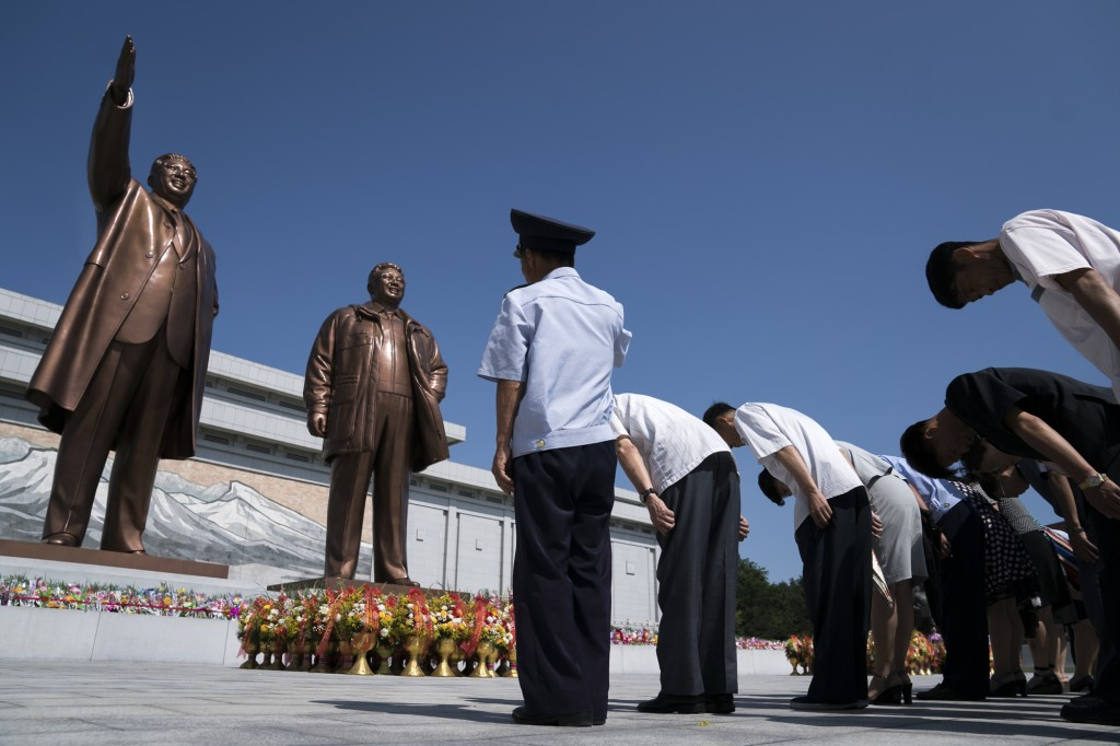 In this Saturday, July 7, 2018, file photo, people pay their respects in front of bronze statues of the late leaders Kim Il Sung, left, and Kim Jong I