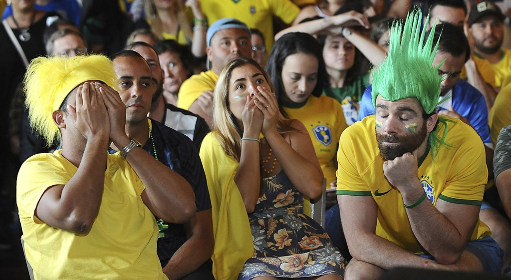 At the Tropical Cafe in Framingham, Mass., Peter, left, and Bruna Rugg, center, of Worcester, Mass., and other Brazilian soccer fans react with dismay...