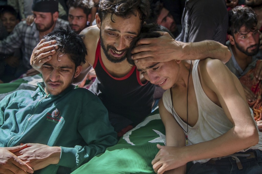 In this Saturday, July 7, 2018, file photo, relatives of Kashmiri civilians grieve near their dead bodies during a joint funeral procession in Hawoora