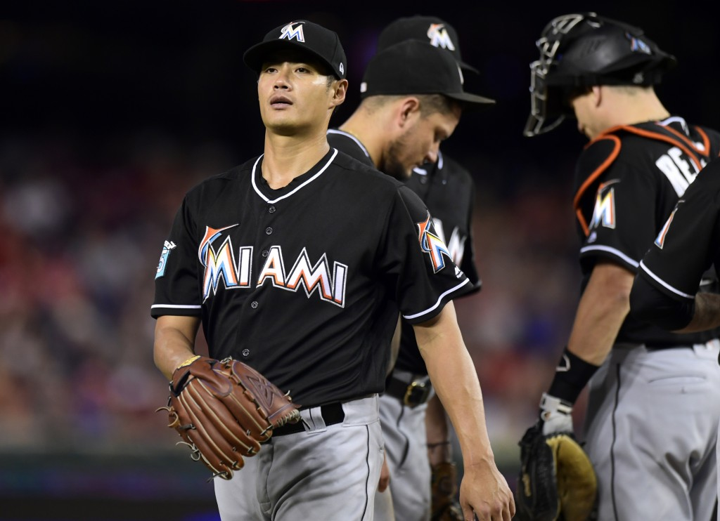 Miami Marlins starting pitcher Wei-Yin Chen, left, of Taiwan, leaves the field during the fifth inning of a baseball game against the Washington Natio
