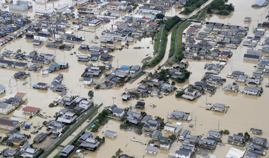In this Sunday, July 8, 2018, file photo, houses are submerged by muddy water following heavy rains in Kurashiki city, Okayama prefecture, southwester