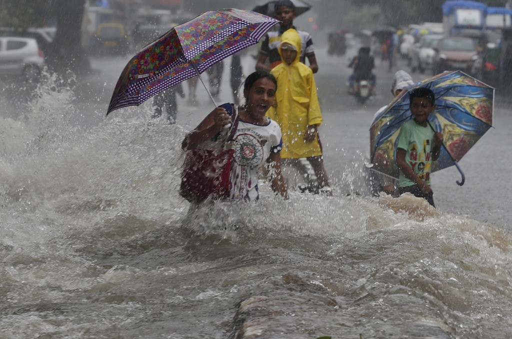 In this Sunday, July 8, 2018, file photo, a woman walking through a water logged street, reacts as a truck driving past creates a wave of ripples prio