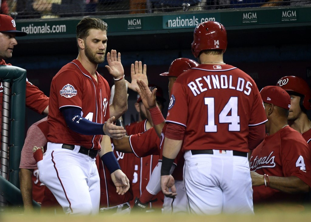 Washington Nationals Bryce Harper, second from left, reaches out to congratulate teammate Mark Reynolds, (14) after Reynolds hit a two-run home run ag