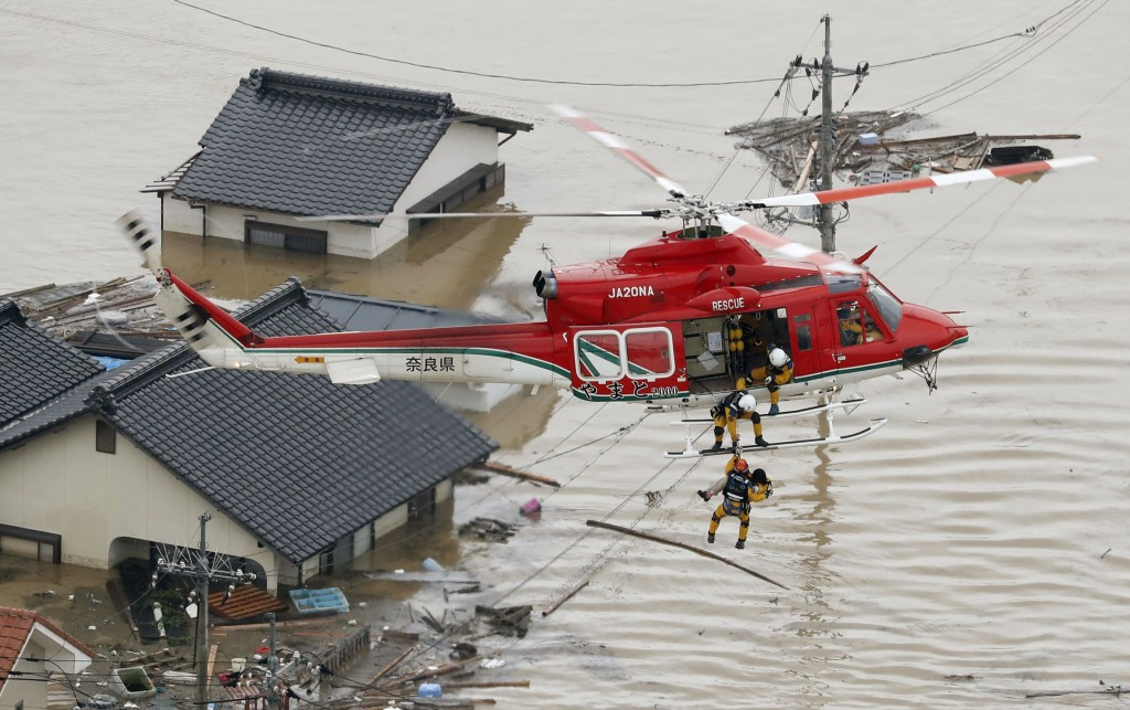 In this July 7, 2018, file photo, a resident is rescued in a flooded area in Kurashiki, Okayama prefecture, following heavy rains. Heavy rainfall hamm
