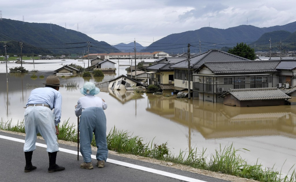 In this Sunday, July 8, 2018, file photo, residents look at half submerged houses in floodwater from heavy rains, in Kurashiki, Okayama prefecture, so
