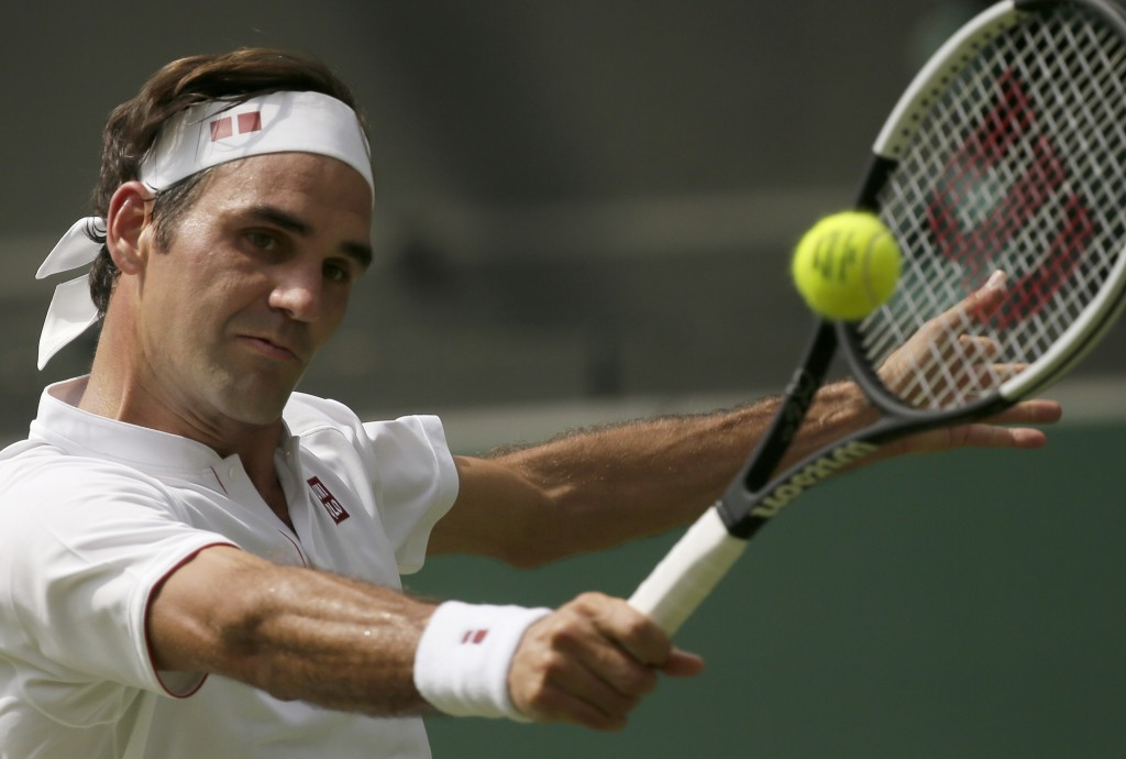 Roger Federer of Switzerland returns the ball to France's Adrian Mannarino during their men's singles match, on day seven of the Wimbledon Tennis Cham...