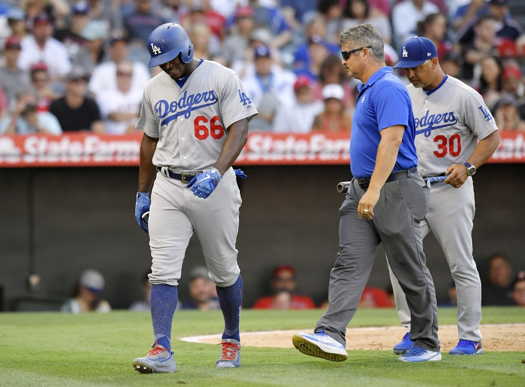 Los Angeles Dodgers' Yasiel Puig, left, walks off the field as a trainer, center, and manager Dave Roberts, right, follow after Puig was injured while