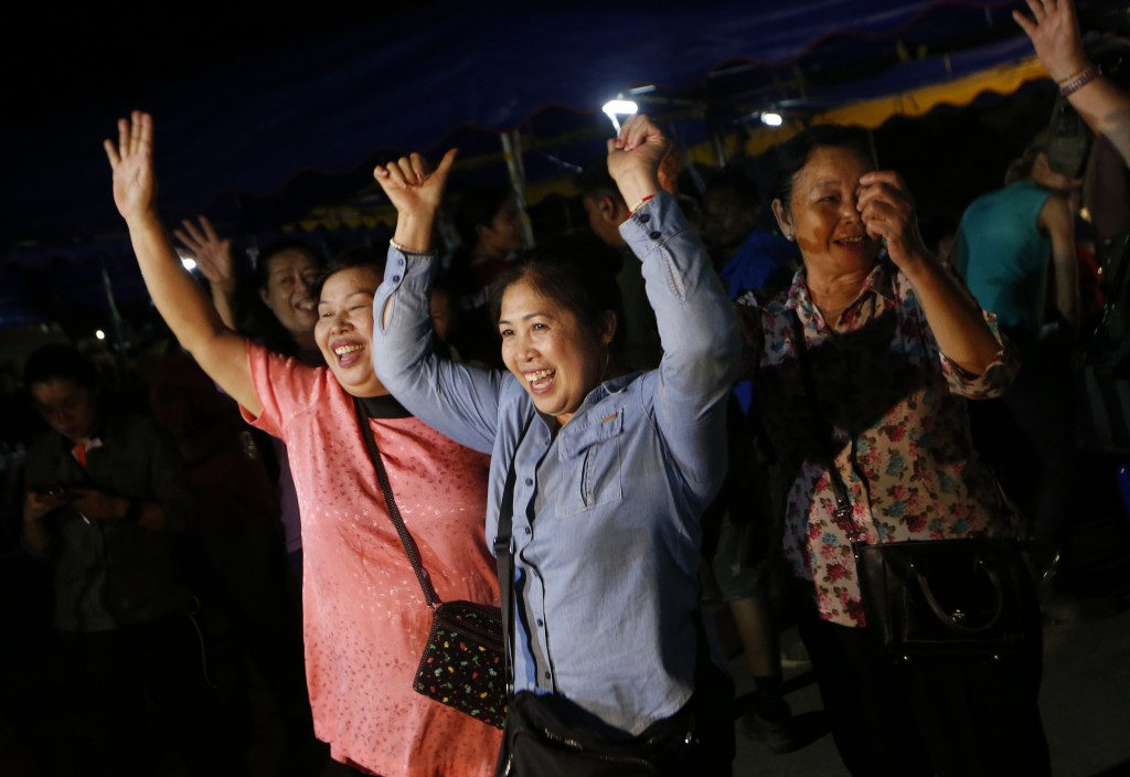 In this Tuesday, July 10, 2018, file photo, people celebrate after divers evacuated some of the 12 boys and their coach trapped at Tham Luang cave in