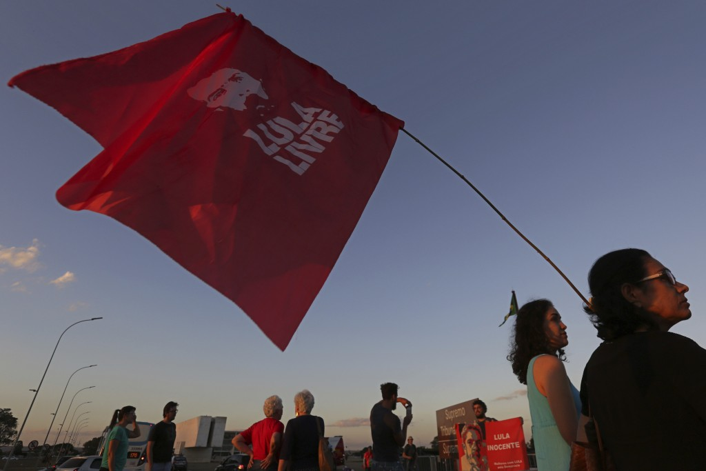 "A supporter of Brazil's former President Luiz Inacio Lula da Silva carries a flag with text written in Portuguese that reads ""Free Lula"" during a prot"