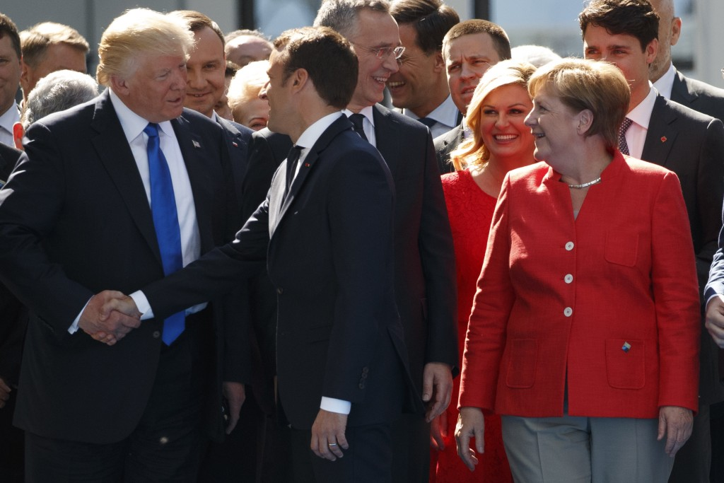 FILE - In this Thursday, May 25, 2017 file photo, German Chancellor Angela Merkel, right, watches as U.S. President Donald Trump, left, shakes hands w
