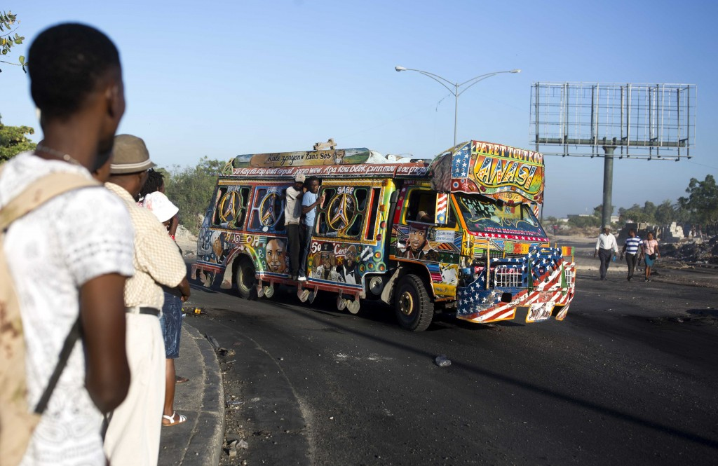 A painted bus filled with passengers makes its way along the street on the second day of a nationwide, general strike in Port-au-Prince, Haiti, early