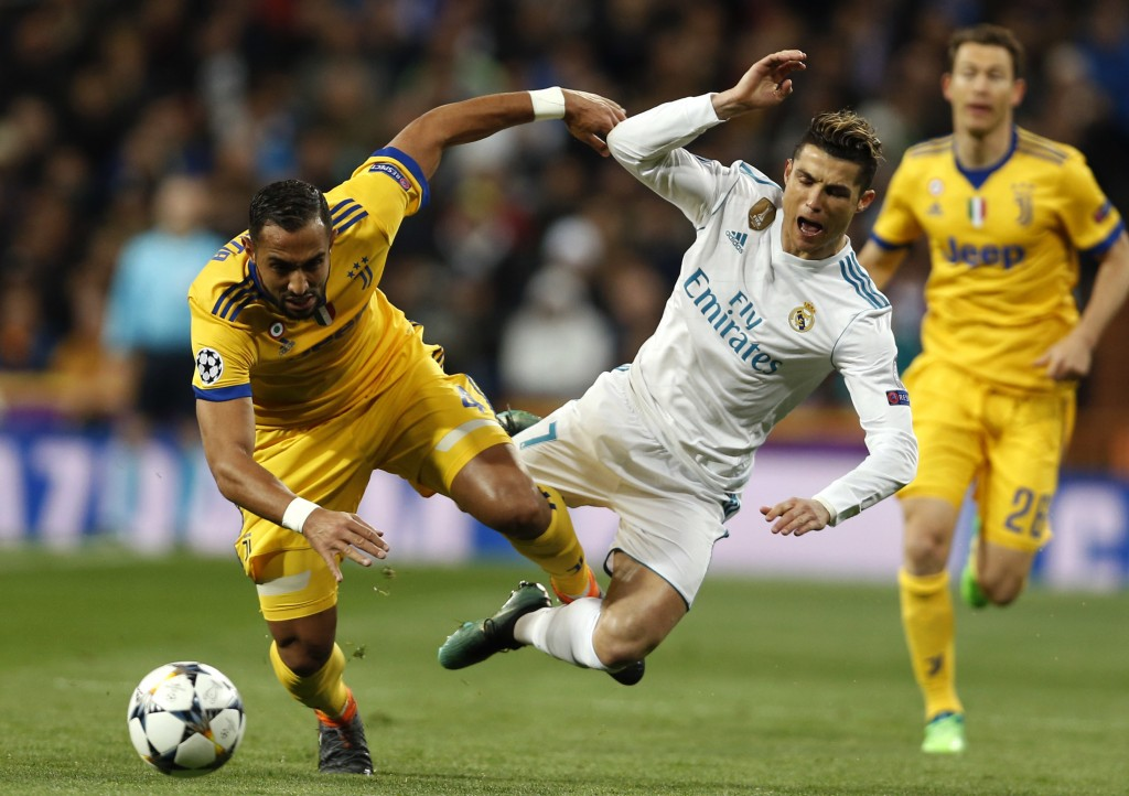FILE - In this Wednesday, April 11, 2018 file photo Real Madrid's Cristiano Ronaldo is tackled by Juventus' Medhi Benatia during a Champions League qu