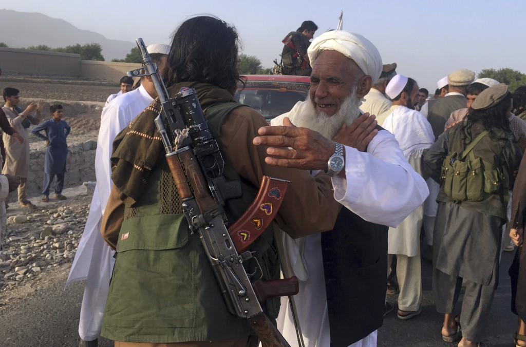 FILE - In this June 16, 2018 file photo, Taliban fighters gather with residents to celebrate a three-day cease fire marking the Islamic holiday of Eid...
