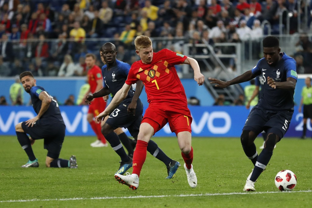Belgium's Kevin De Bruyne, center, and France's Samuel Umtiti challenge for the ball during the semifinal match between France and Belgium at the 2018