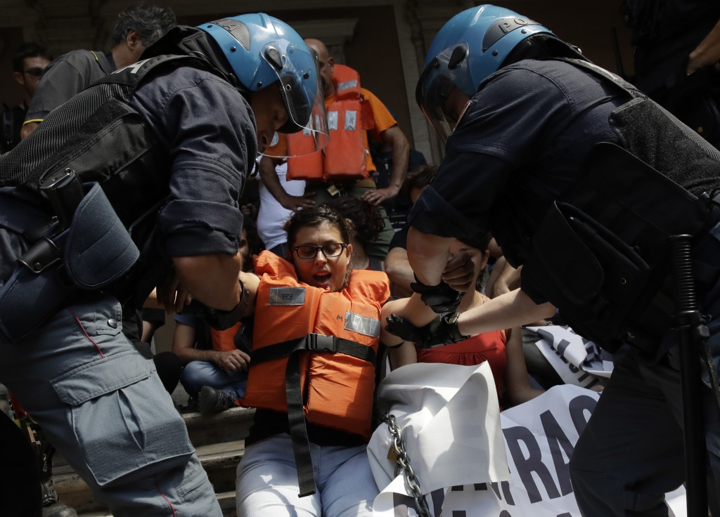 Protesters are dragged away by Italian police outside the Ministry of Transport in Rome, Wednesday, July 11, 2018. Dozens of protesters chained themse