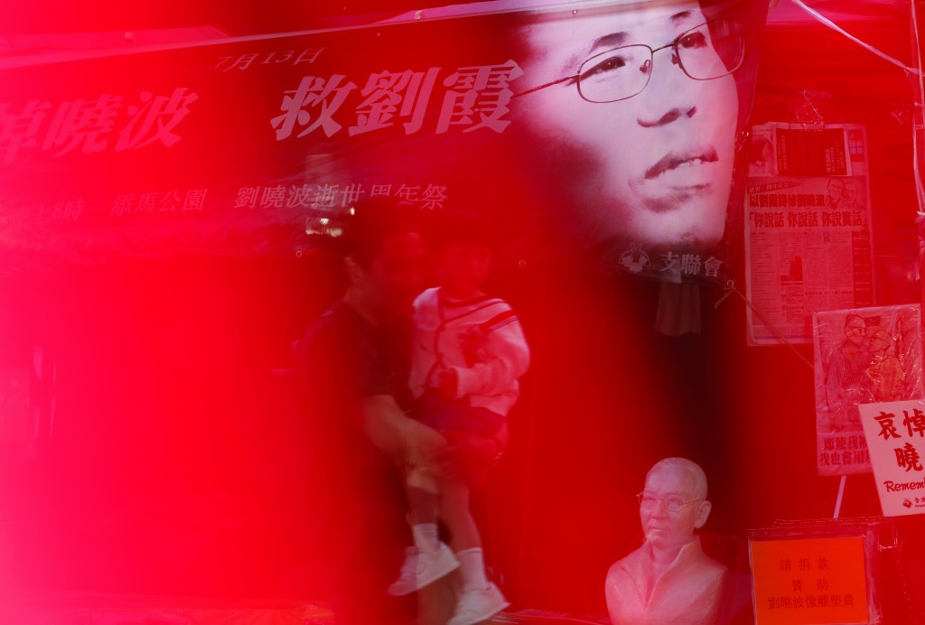 In this Tuesday, July 10, 2018, file photo, an image of Liu Xia, wife of the late Nobel Peace Laureate Liu Xiaobo, is displayed at a booth to collect