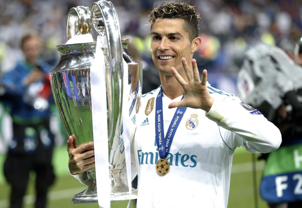 FILE - In this Saturday, May 26, 2018 file photo Real Madrid's Cristiano Ronaldo celebrates with the trophy after winning the Champions League Final s