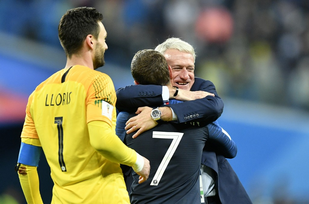 France head coach Didier Deschamps, right, hugs Antoine Griezmann after their team advanced to the final after the semifinal match between France and