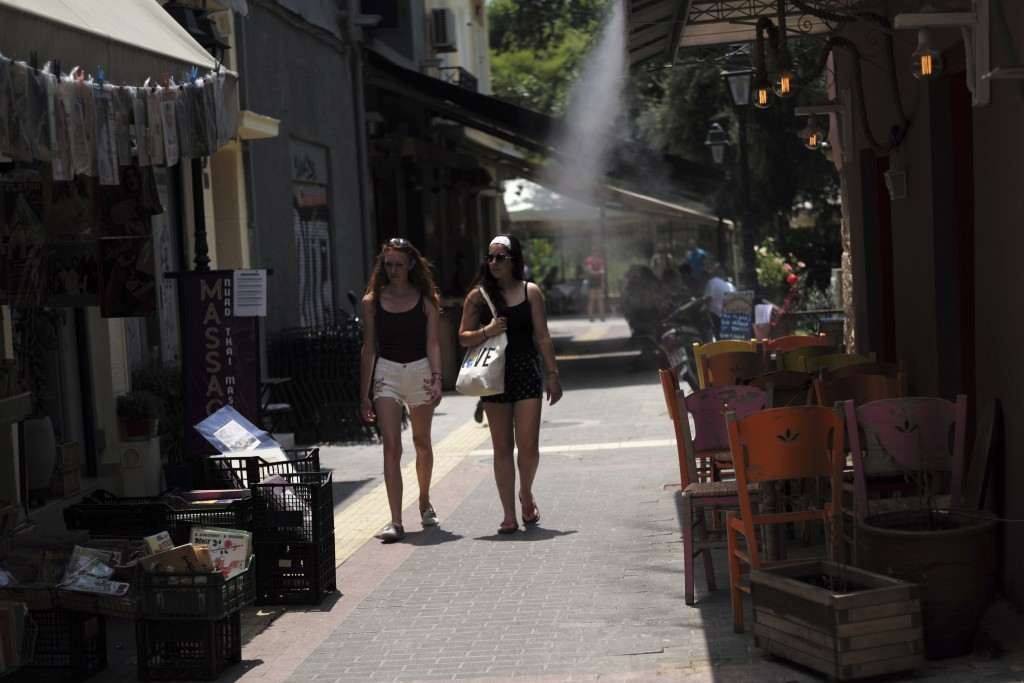 Women walk by a spray from a cooling system of a restaurant in the the Monastiraki district of central Athens on Wednesday, July 11, 2018. European Co