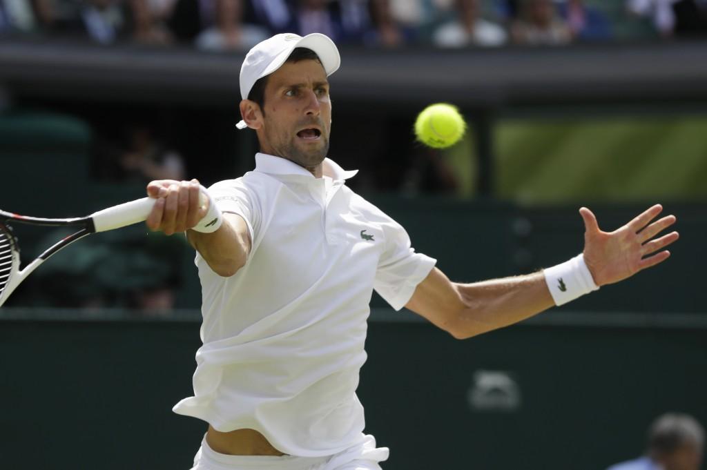 Novak Djokovic of Serbia returns the ball to Kei Nishikori of Japan during their men's quarterfinal match at the Wimbledon Tennis Championships in Lon