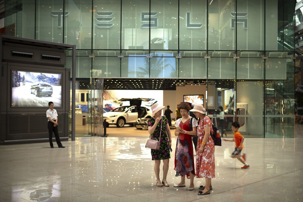 FILE - In this July 5, 2018, file photo, women look at a smartphone outside of a Tesla showroom at an upscale shopping mall in Beijing. Electric car p