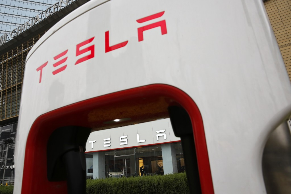 FILE - In this April 5, 2018, file photo, a sales person stands inside a Tesla electric vehicle showroom in Beijing. Electric car producer Tesla will