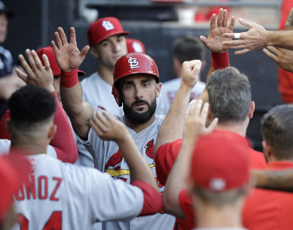 St. Louis Cardinals' Matt Carpenter celebrates in the dugout after scoring on a single by Jose Martinez during the third inning of a baseball game aga