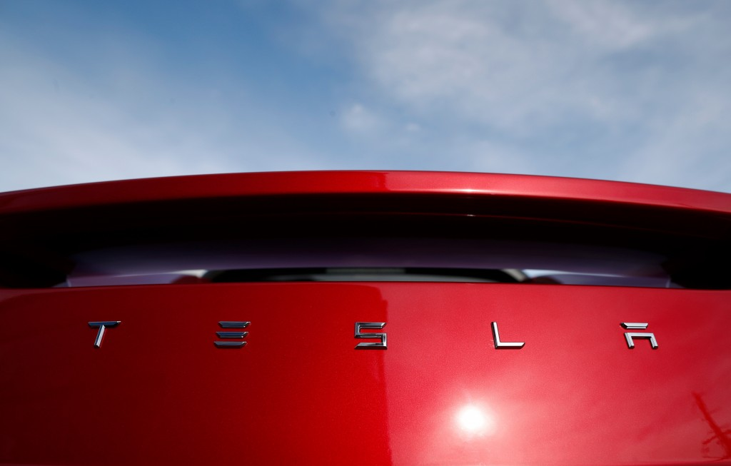 FILE - In this April 15, 2018, file photo, the sun shines off the rear deck of a roadster on a Tesla dealer's lot in the south Denver suburb of Little