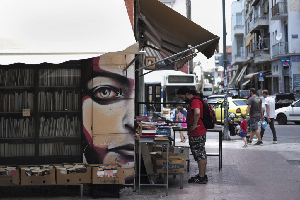 A man look sat second hand books for sale in the Monastiraki district of central Athens, Wednesday, July 11, 2018. European Commission officials say G