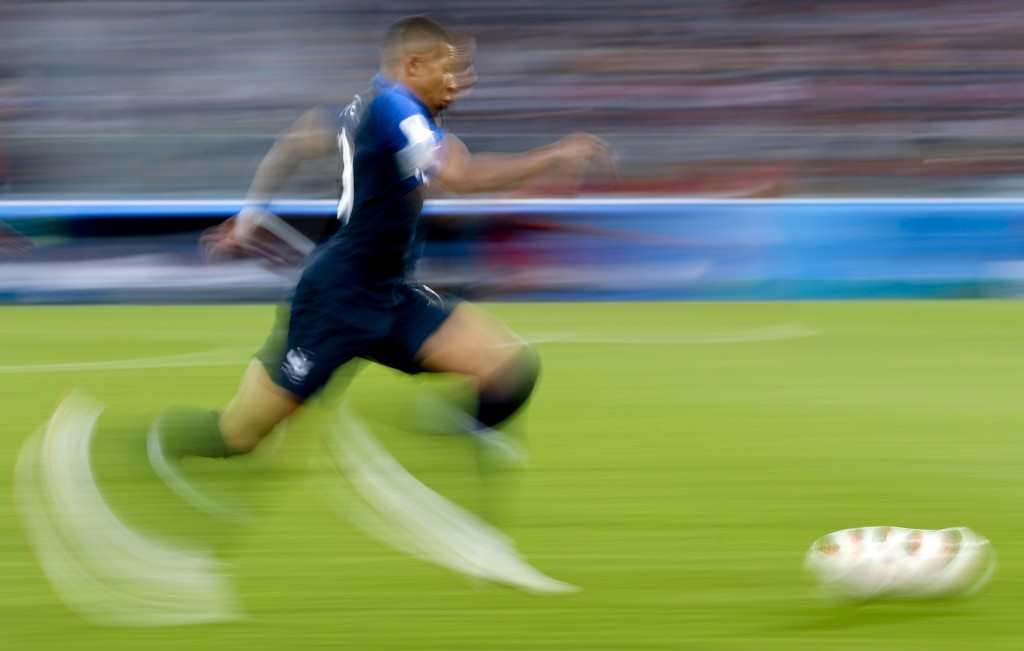 In this photo taken with slow shutter speed France's Kylian Mbappe runs with the ball during the semifinal match between France and Belgium at the 201
