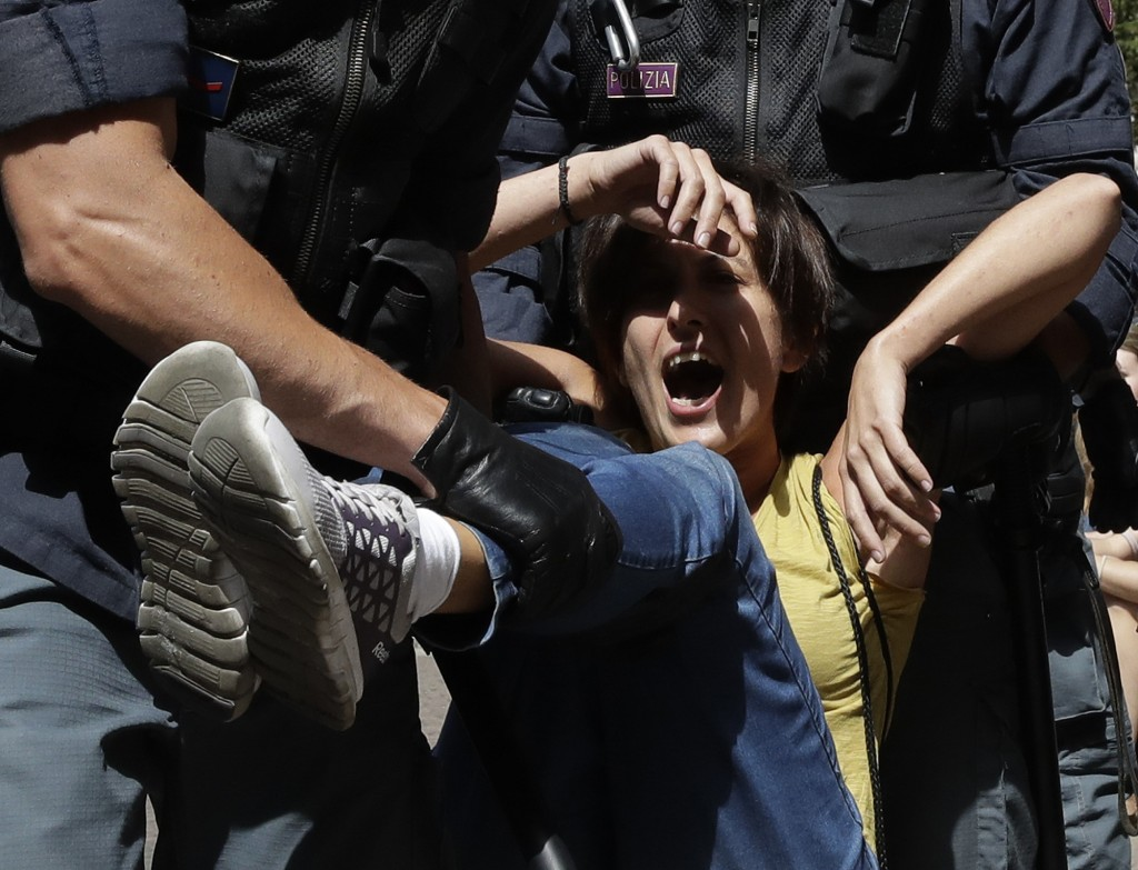 A protester shouts as she is dragged away by Italian police outside the Ministry of Transport in Rome, Wednesday, July 11, 2018. Dozens of protesters