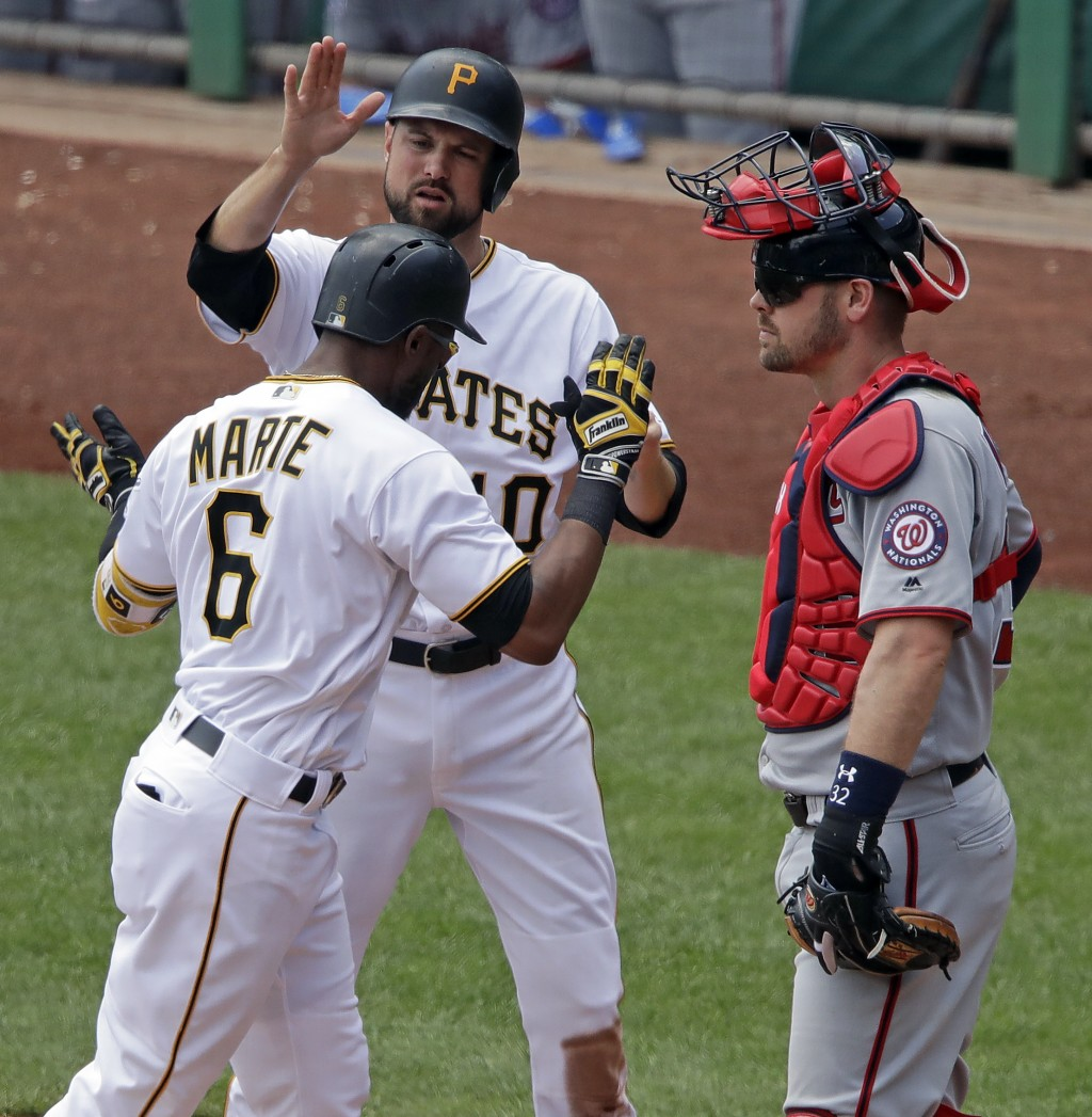 Washington Nationals catcher Matt Wieters, left, waits as Pittsburgh Pirates' Starling Marte (6) celebrates with Jordy Mercer after hitting a two-run