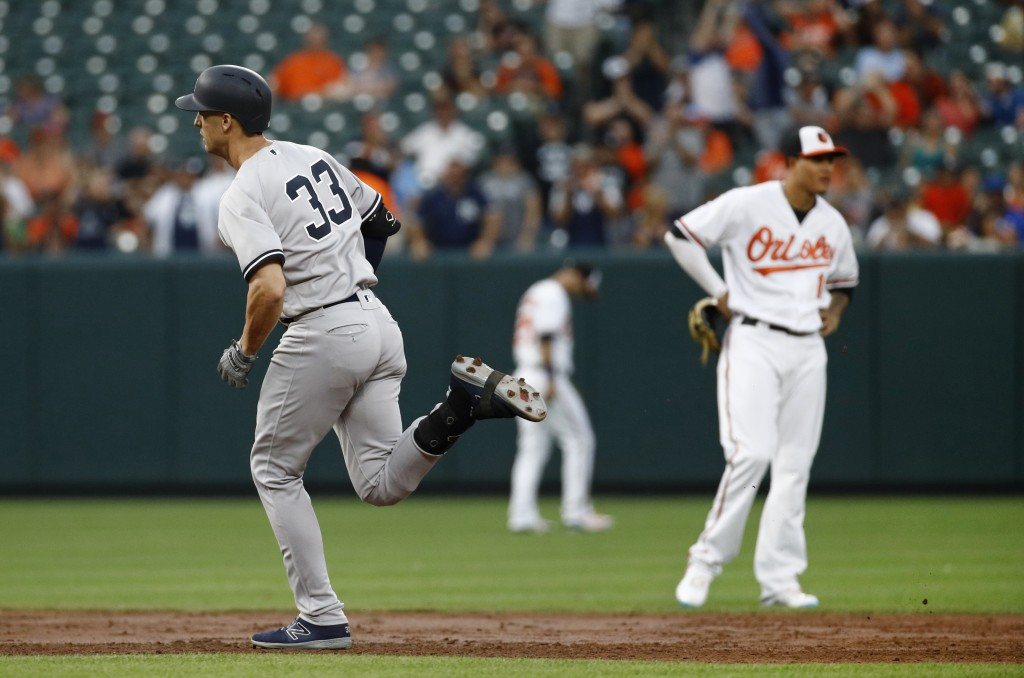 New York Yankees' Greg Bird, left, rounds the bases past Baltimore Orioles shortstop Manny Machado after hitting a grand slam during the third inning