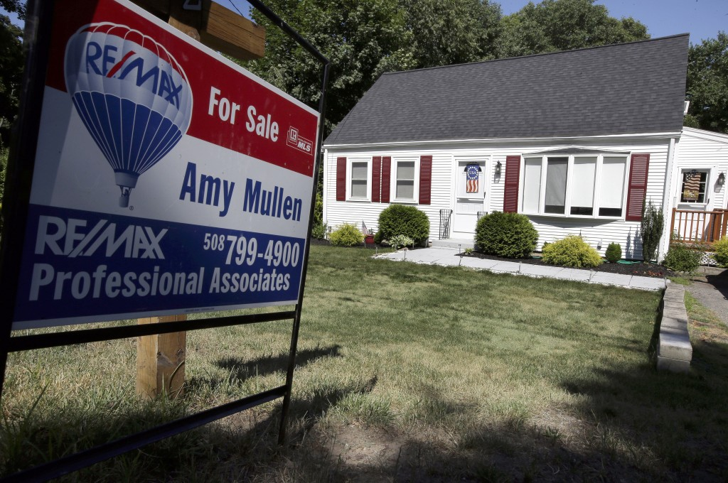 In this Monday, July 9, 2018, photo a for sale sign stands outside a pre-existing home, in Walpole, Mass. On Thursday, July 12, Freddie Mac reports on