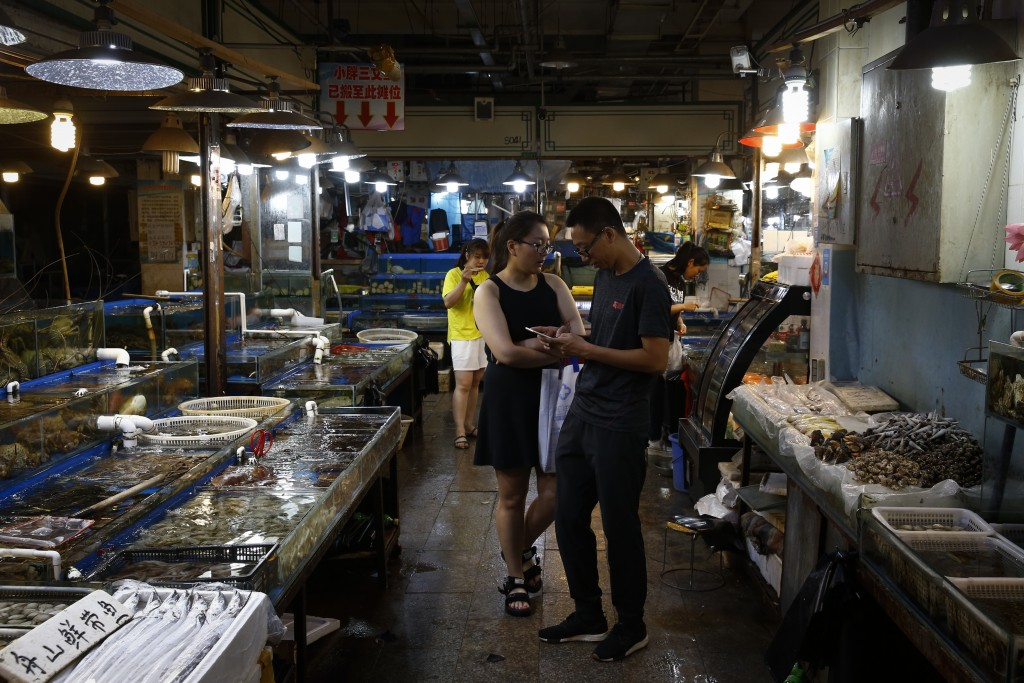 A Chinese couple shop for seafoods at the Jingshen seafood market in Beijing, Thursday, July 12, 2018. China's government vowed on Wednesday to take ""