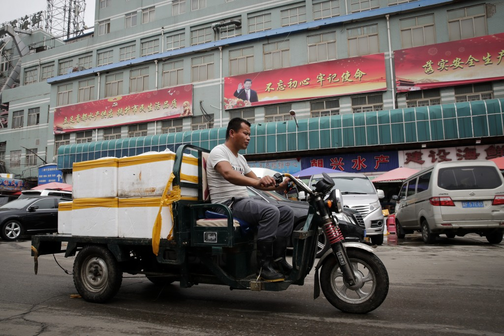 A man rides a motor-tricycle loaded with seafood products past by a billboard featuring Chinese President Xi Jinping and the government propaganda on