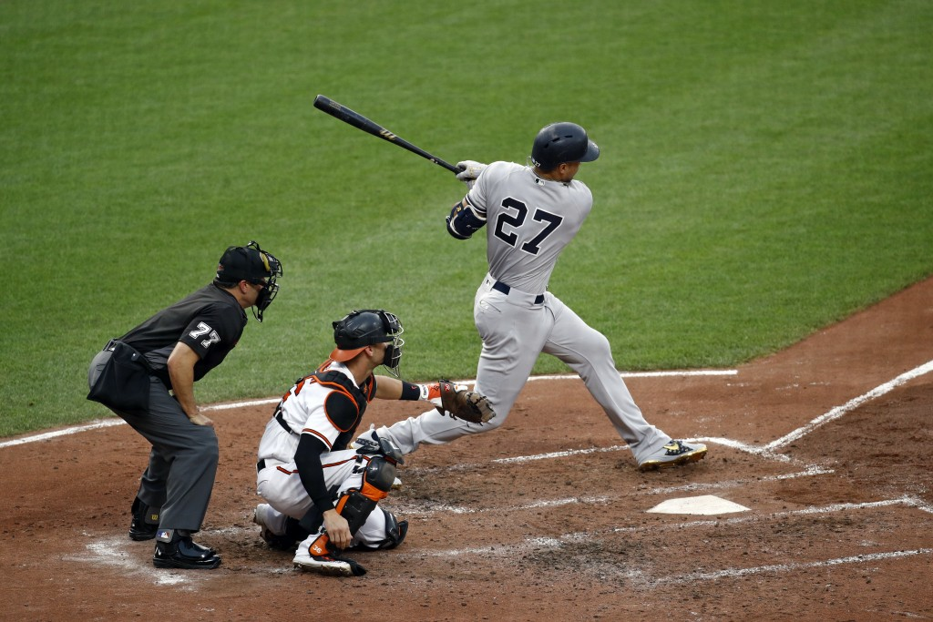 New York Yankees' Giancarlo Stanton follows through on an RBI single in front of umpire Jim Reynolds and Baltimore Orioles catcher Caleb Joseph during